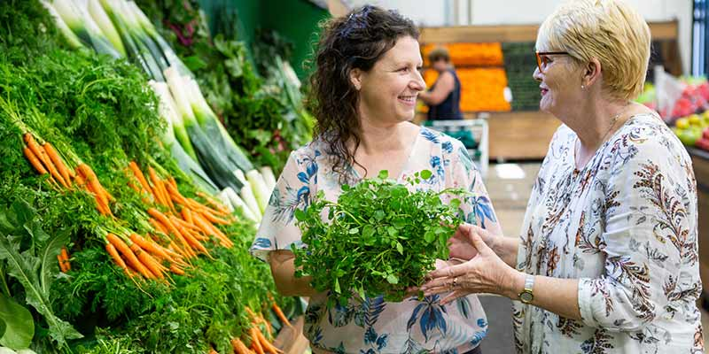 Image of a women with brown curly hair and a lady with short blonde hair smiling and holding green vegetables