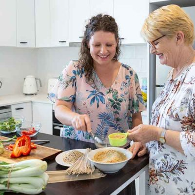 Image of women with curly brown haire and women with short, strait blond hair and glasses measuring food in the kitchen.