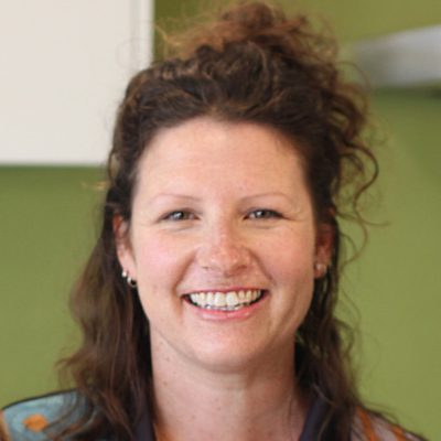 Image of a women with brown curly smiling