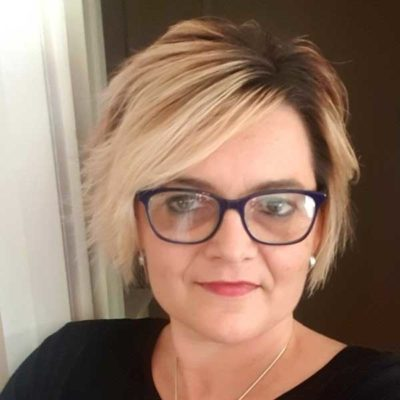 Image of a women with short blonde hair, glasses and black jumper